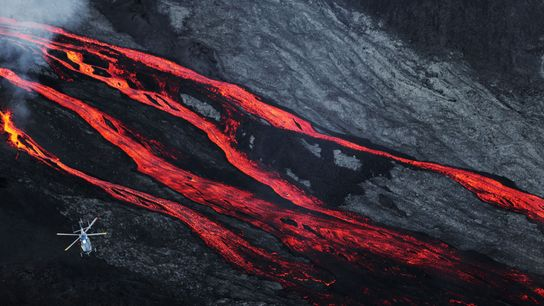 A helicopter soars above Piton de la Fournaise volcano on Réunion island in the Indian Ocean.