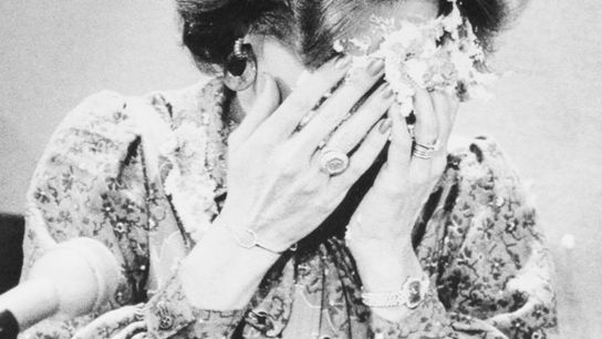 Singer-evangelist Anita Bryant covers her face after being hit with a pie by a man posing ...