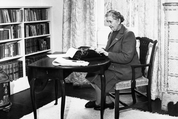 Agatha Christie writing at her desk.