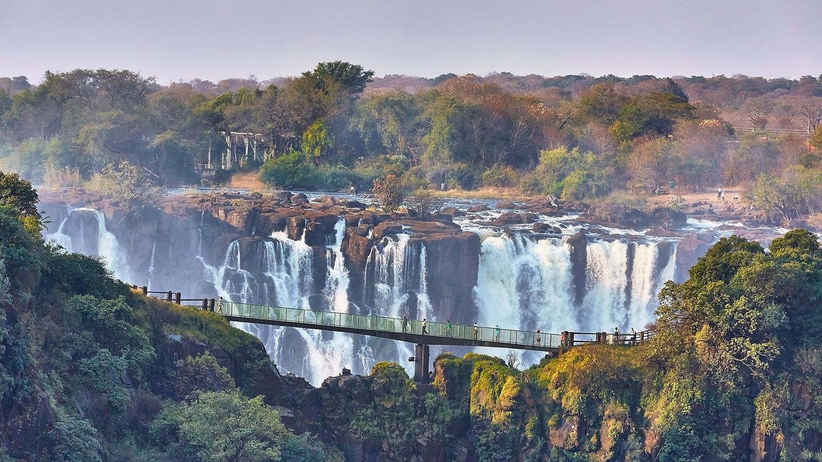 Tourists cross the Knife Edge Bridge with the mighty Victoria Falls in the background.