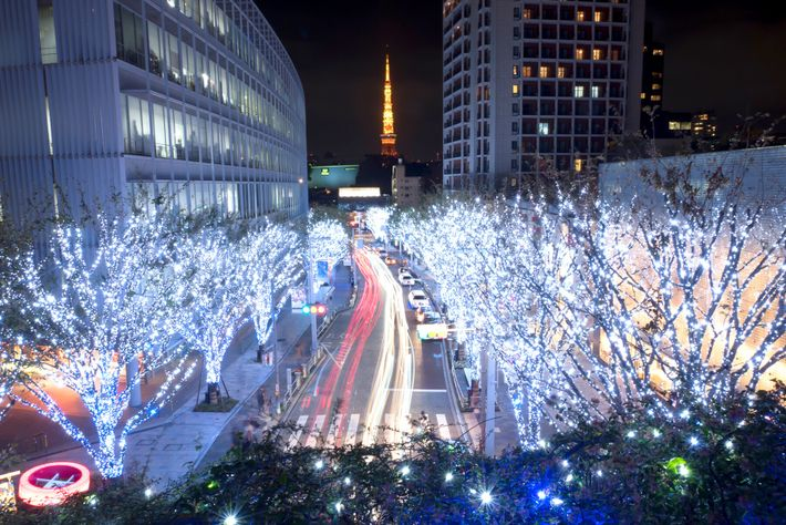 Christmas lights line a street leading in the direction of Tokyo Tower. Japan has adopted many ...