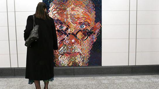 A woman checks out a self-portrait tile mosaic by Chuck Close decorating the 86th St. Q ...