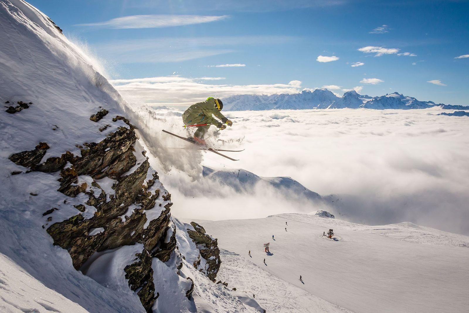 Skier jumping down piste