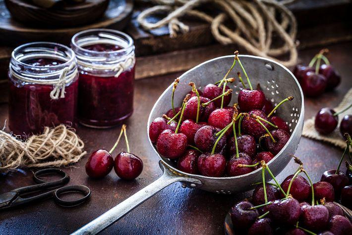 Jam jars and cherries on a farmhouse table.