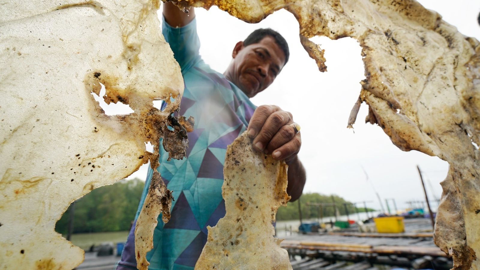 Kamar, an Indonesia fisherman, poses for a snapshot as he holds up the dried skin of ...