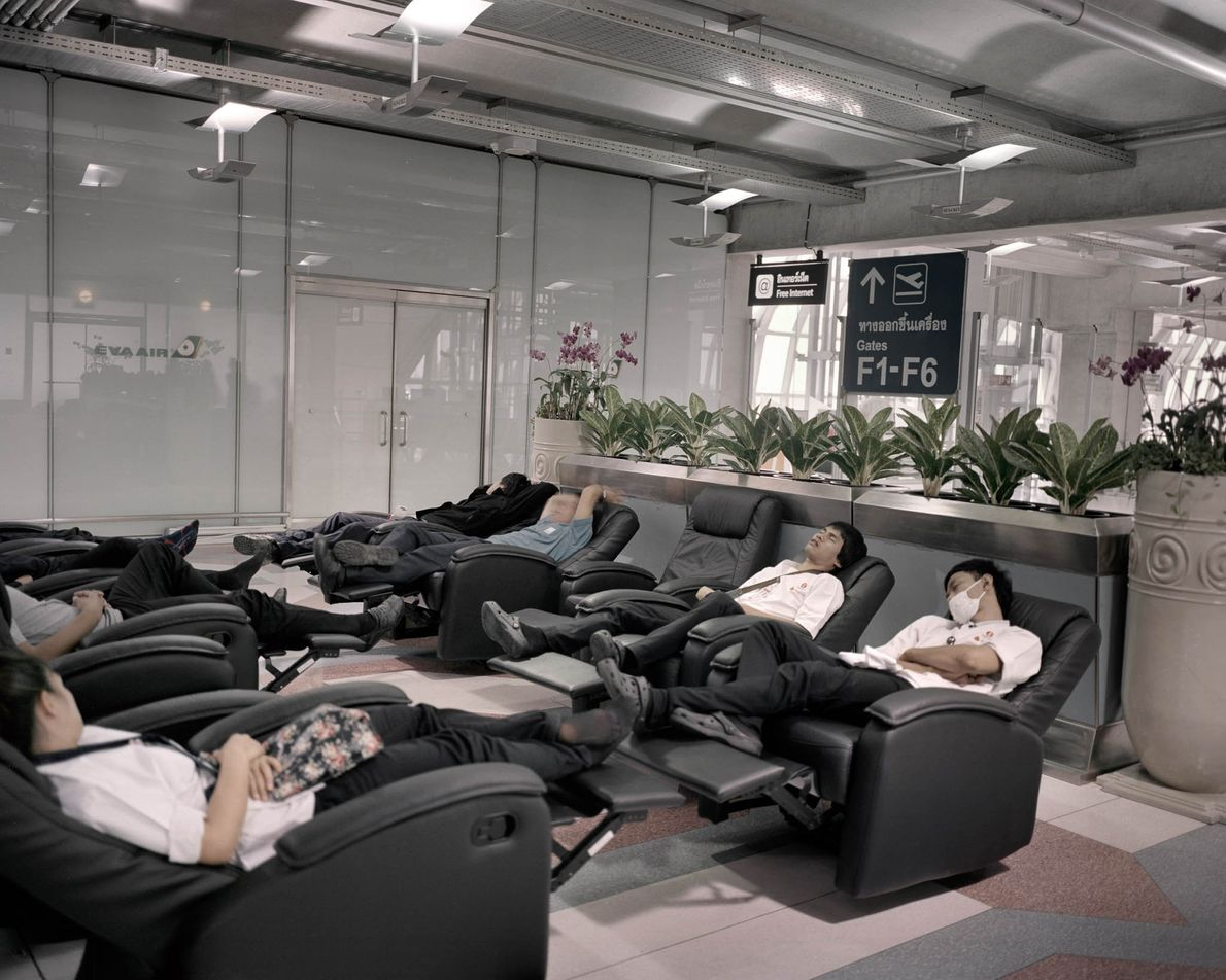 Travellers rest in recliners in Bangkok.