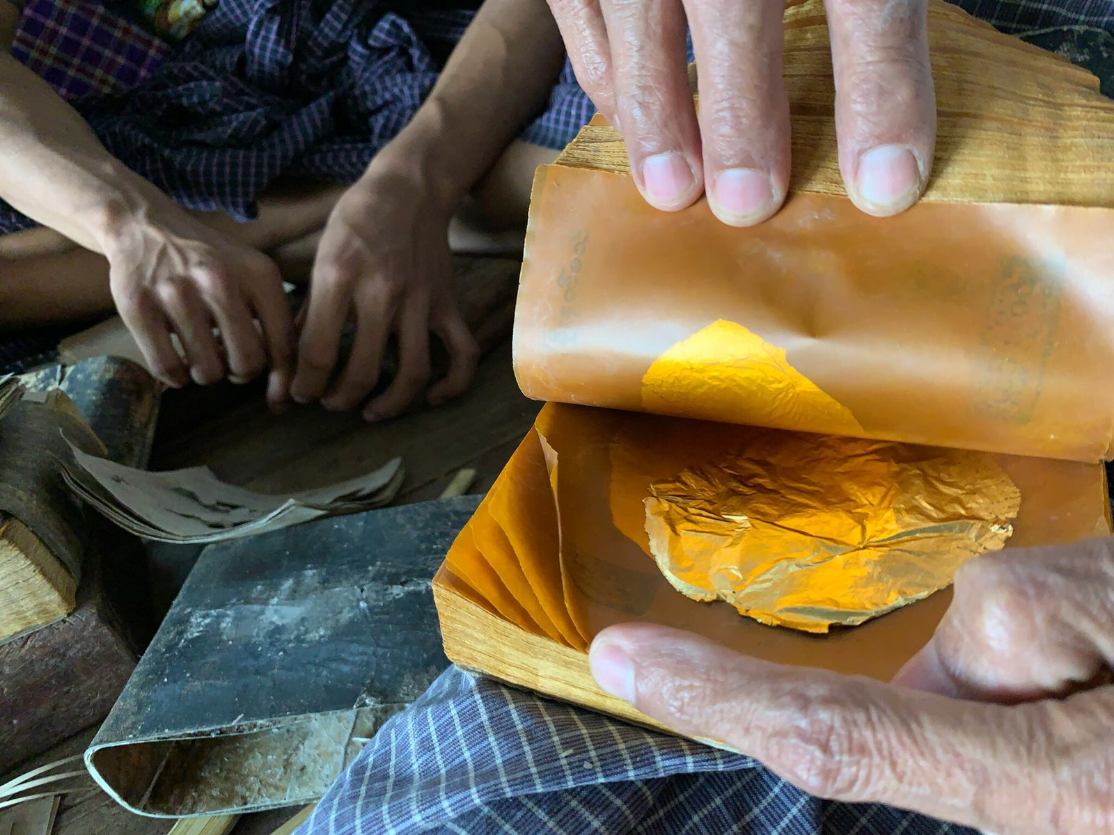 At the King Galon Gold Leaf Workshop, in Mandalay, Myanmar, gold grains stacked between sheets of ...
