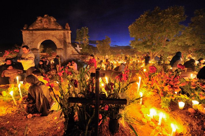 Flowers and candles set the mood during a Day of the Dead vigil at a cemetery ...