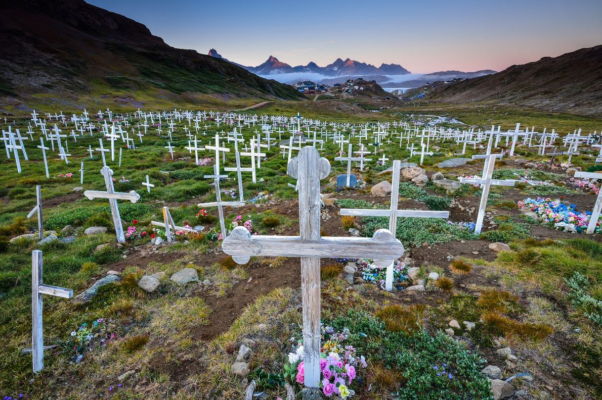 Wooden crosses and bright flowers fill a cemetery on the outskirts of Tasiilaq, Greenland.