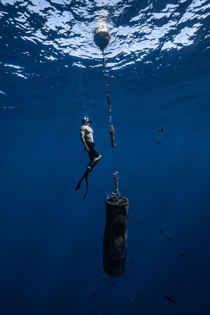 A member of Lecomte's team inspects Drifter C, a buoy used by scientists to track movement ...