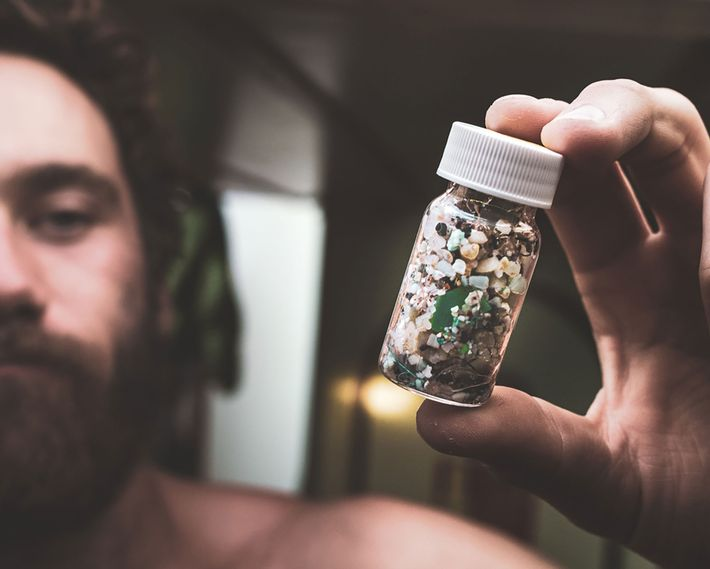 A team member holds a jar of 2,409 pieces of plastic collected from the water in ...