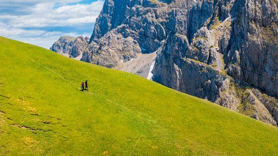 Hikers above the alpine lake of Drakolimni, near Mount Tymfi, Epirus. The lake takes its name ...