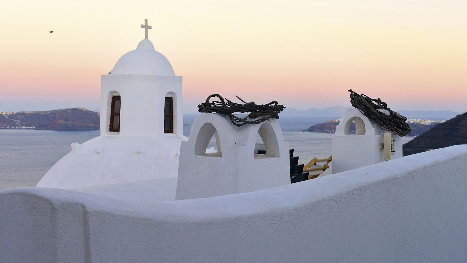 Sunrise in Santorini, Greece, as the morning light lays a shine on the Cycladic whites.