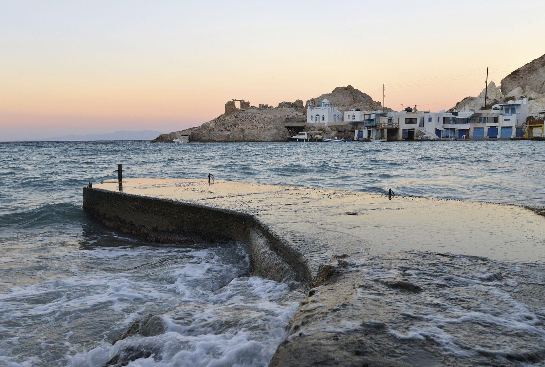 The sun sets on a fishing harbour, Milos