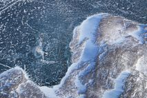 Sea ice meets land as seen from a research aircraft over Greenland. Greenland's ice sheet is ...