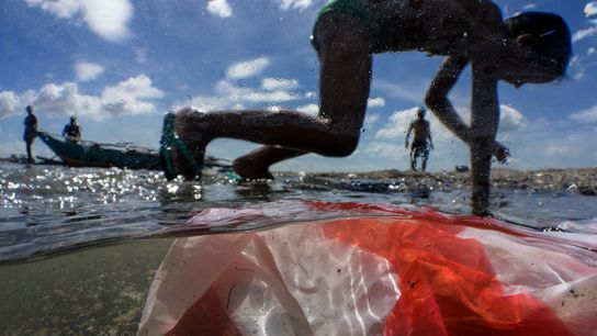 Children play on the shore of Manila Bay in the Philippines, which is often marred by ...