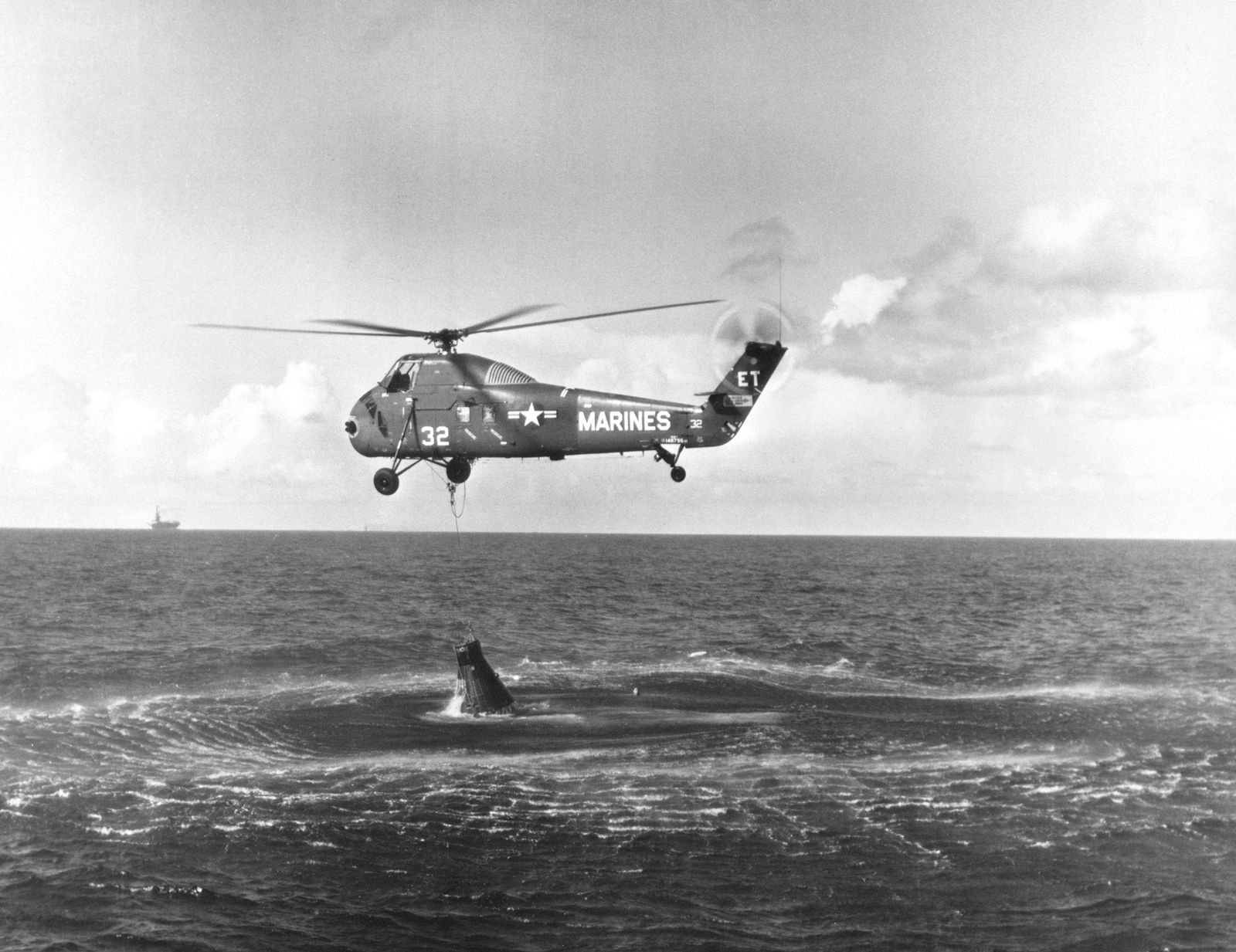 A US Navy helicopter attempts to hoist the stricken Liberty Bell 7 from the water after ...