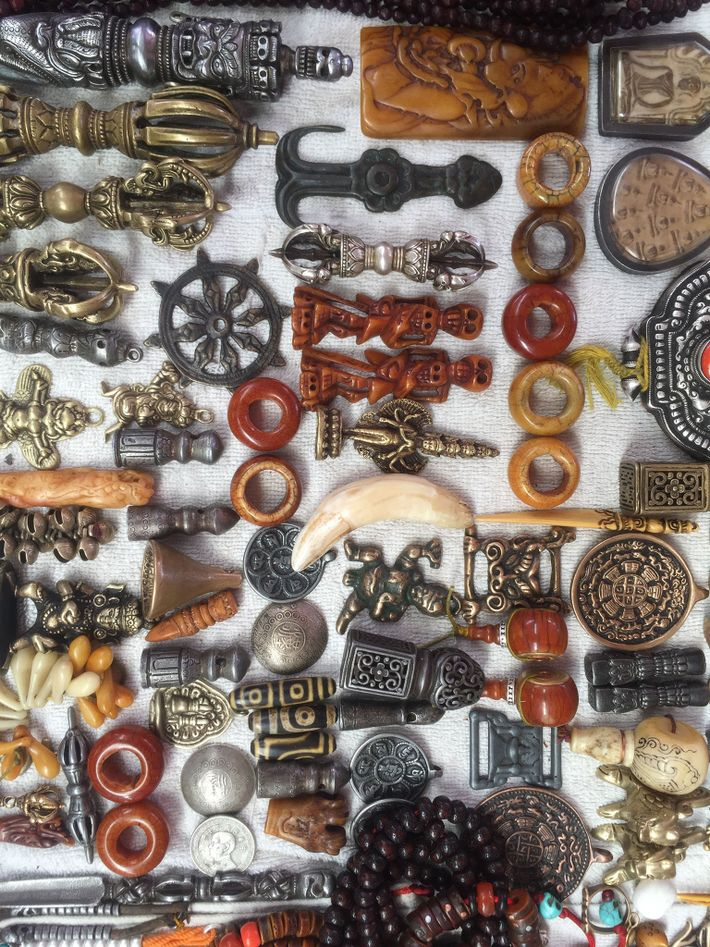 What is represented as a tiger tooth, at centre, is displayed among other trinkets at the ...