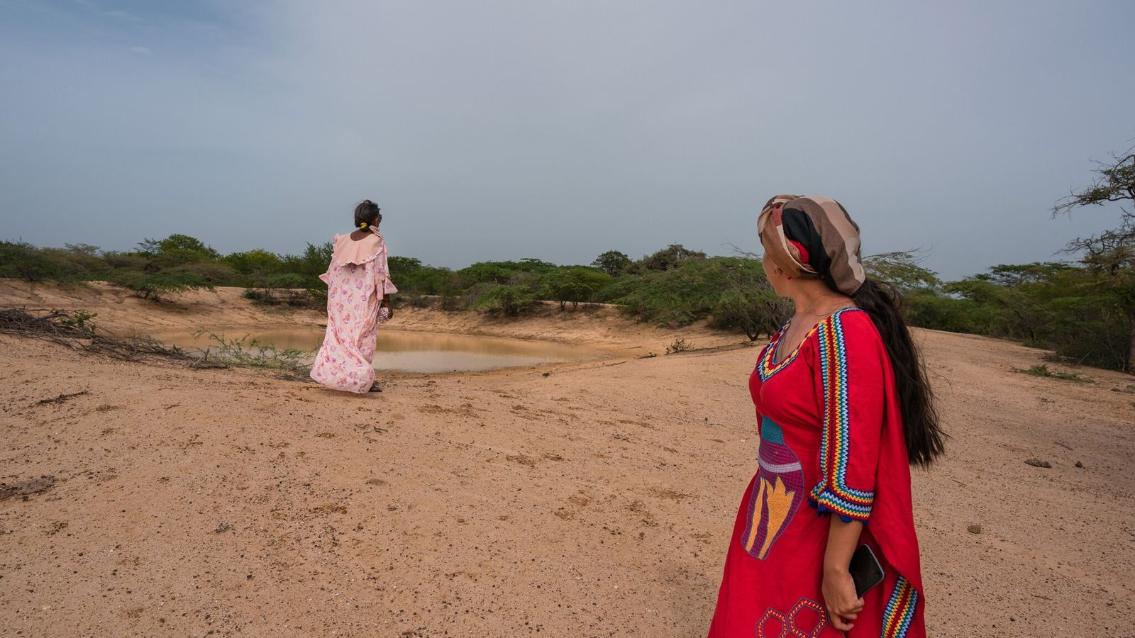 Celia Vangrieken and Yadira Martinez look over a pond that provides limited water for a Wayuu ...