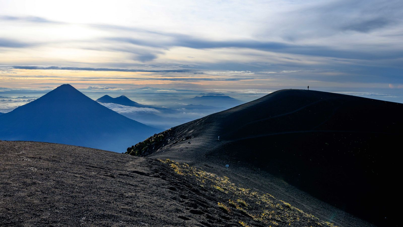 A lone hiker stands atop Acatenango, part of a chain of volcanoes that stretches through the ...