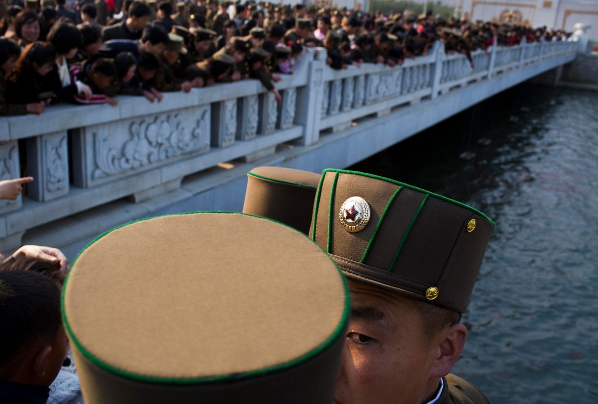 North Korean soldiers and civilians stand on a foot bridge to look at goldfish in a …