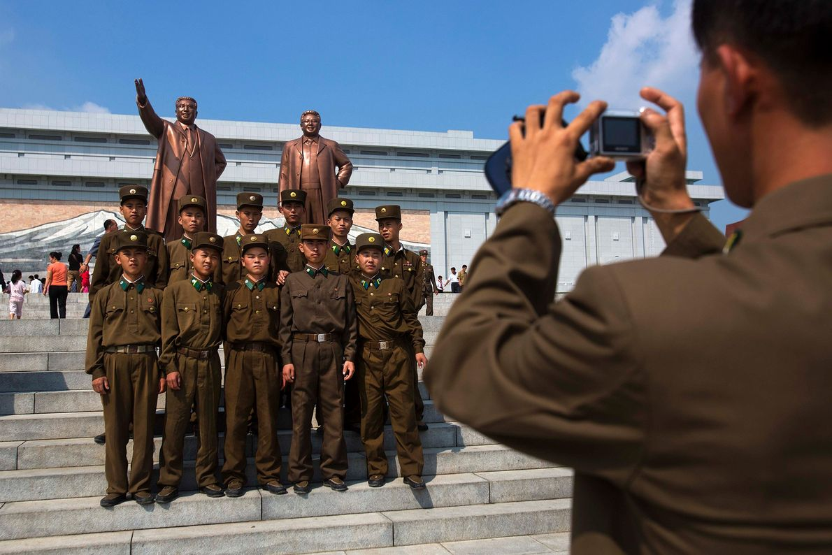 North Korean soldiers pose for a photograph in front of bronze statues of the late leaders ...