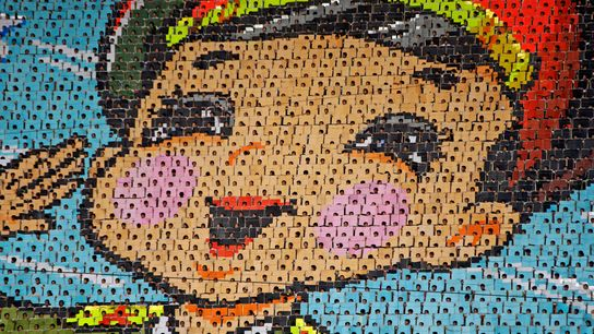 North Koreans flip pages of a colored book to create a mass mosaic during a performance ...