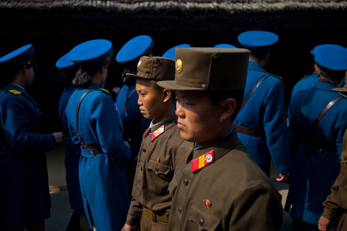 North Korean soldiers, foreground, and North Korean traffic police, background, tour the birthplace of Kim Il ...