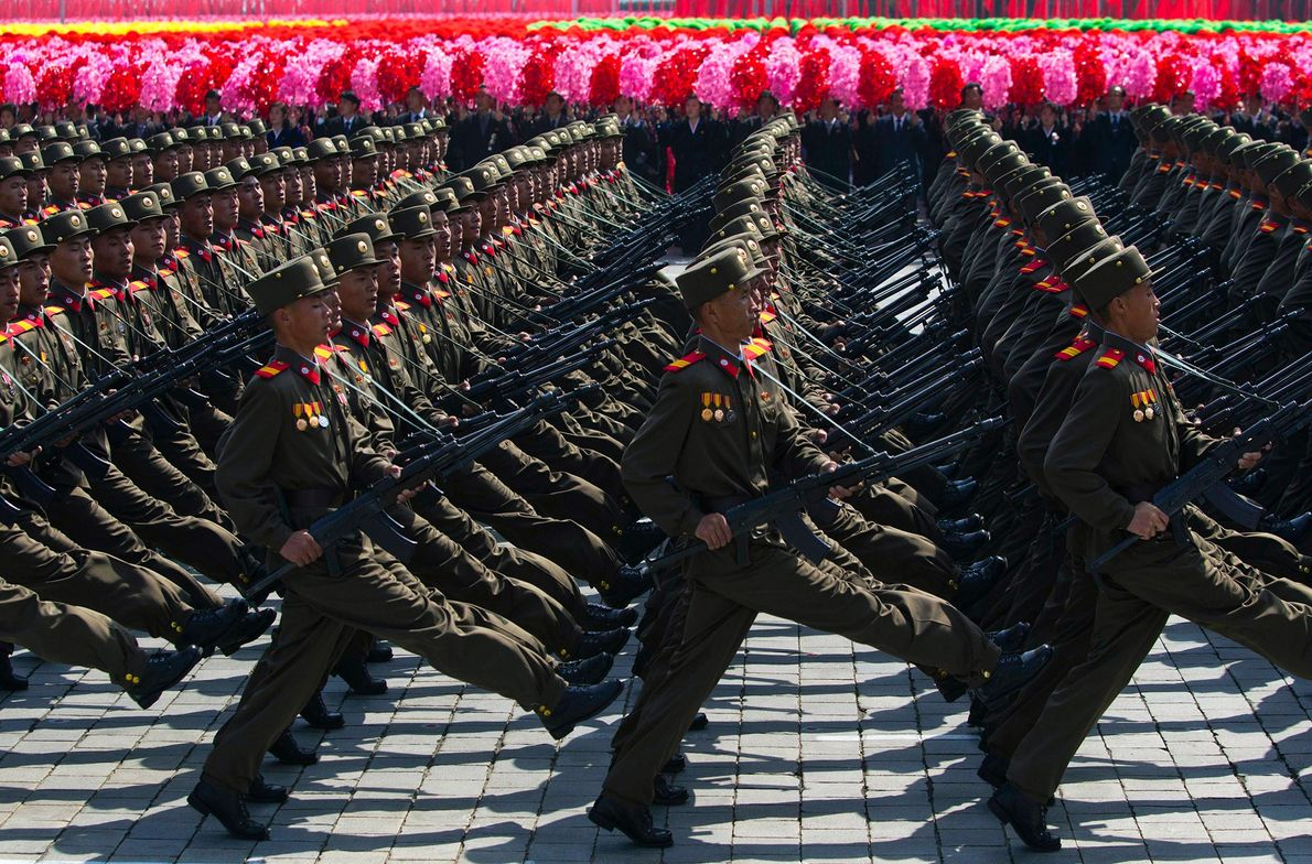 North Korean soldiers march in front of flower waving civilians during a mass military parade in ...