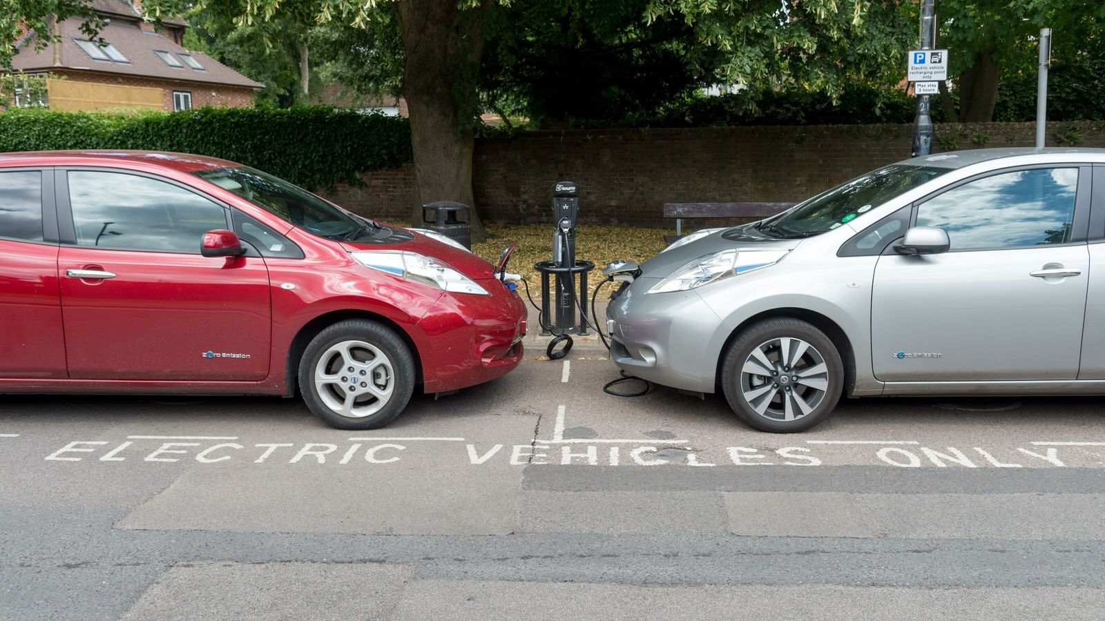 Electric vehicles (EVs) on a kerbside charging point in St Albans, UK. While the cars are ...