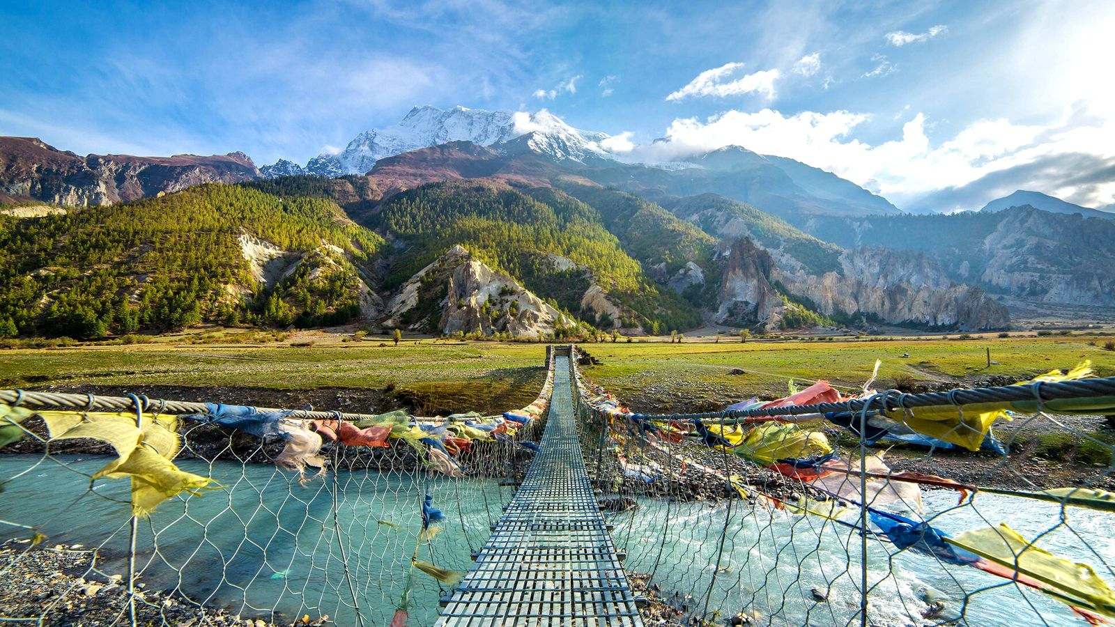 Buddhist prayer flags line a suspension bridge in Nepal's remote Mustang District, a renowned Himalayan trekking ...