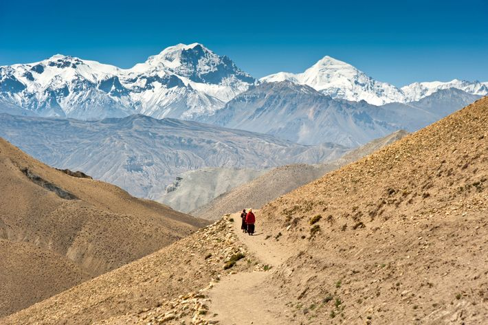 Monks trek through the Mustang region of Nepal, with Himalayan peaks towering in the distance.