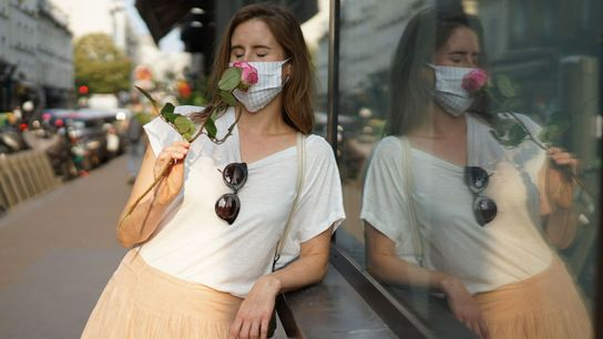A woman wearing a protective mask smells a rose as she wanders through the Paris streets. ...