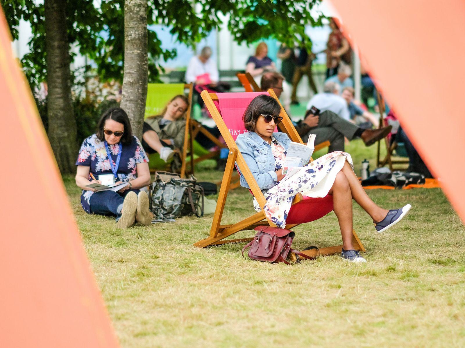 A festival attendeein a deckchair enjoys a book at 2019'sHay Festival, Wales.