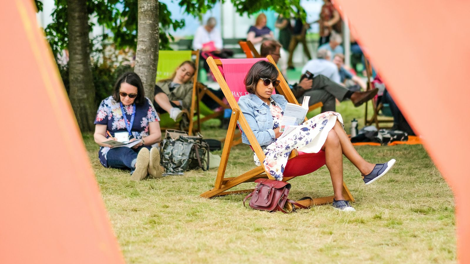 A festival attendee in a deckchair enjoys a book at 2019's Hay Festival, Wales.