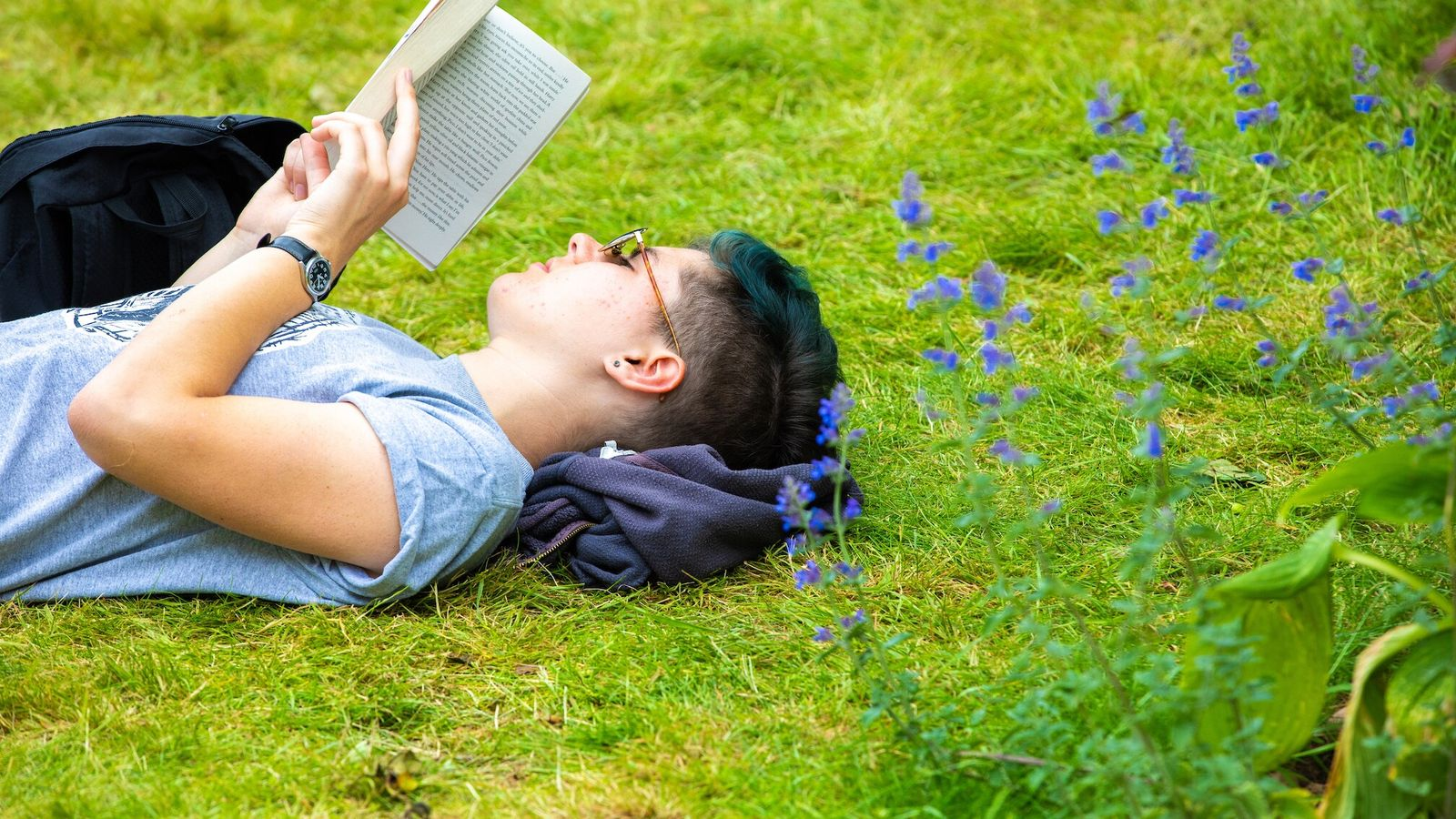 A reader reclines on the grass at a previous Hay Festival, in the Welsh town of ...