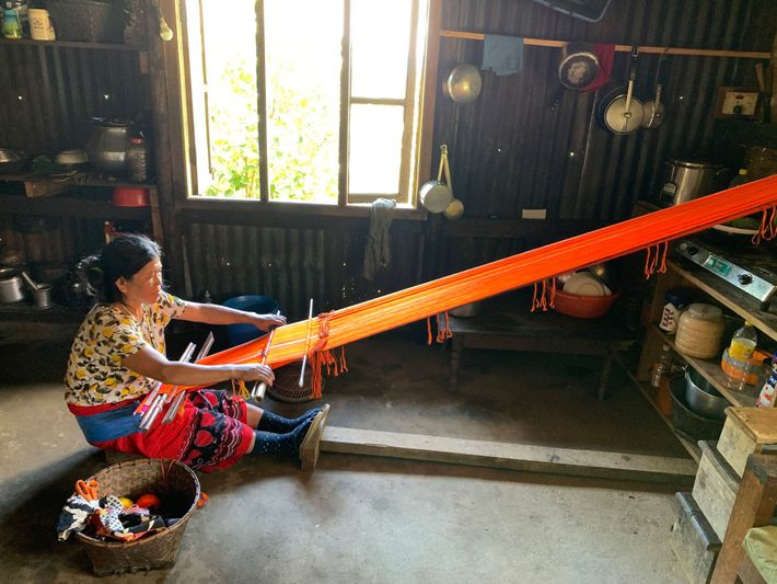 Asinliu Panmei works on a traditional Naga shawl. Many Naga women have looms in their homes. ...