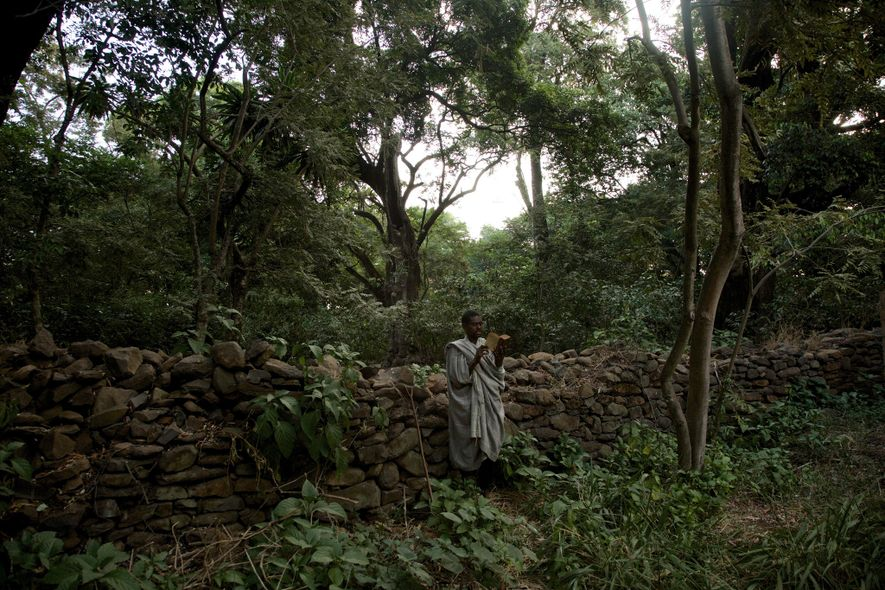 A man prays and reads holy scripture within the churchyard of the Robit Bahita church, near ...
