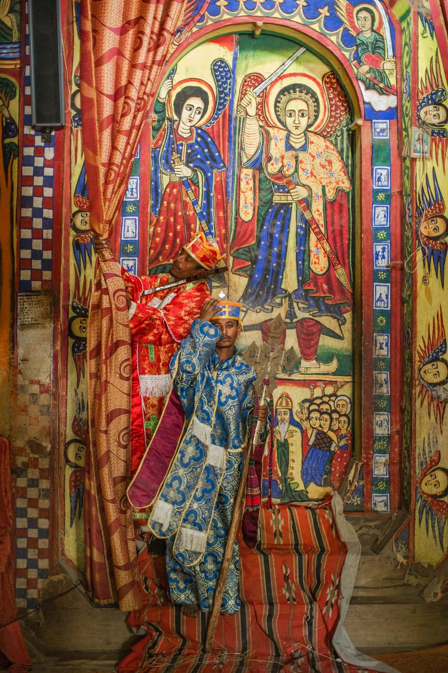 A priest dressed in ceremonial robes stands in front of a vibrant painted mural at the ...