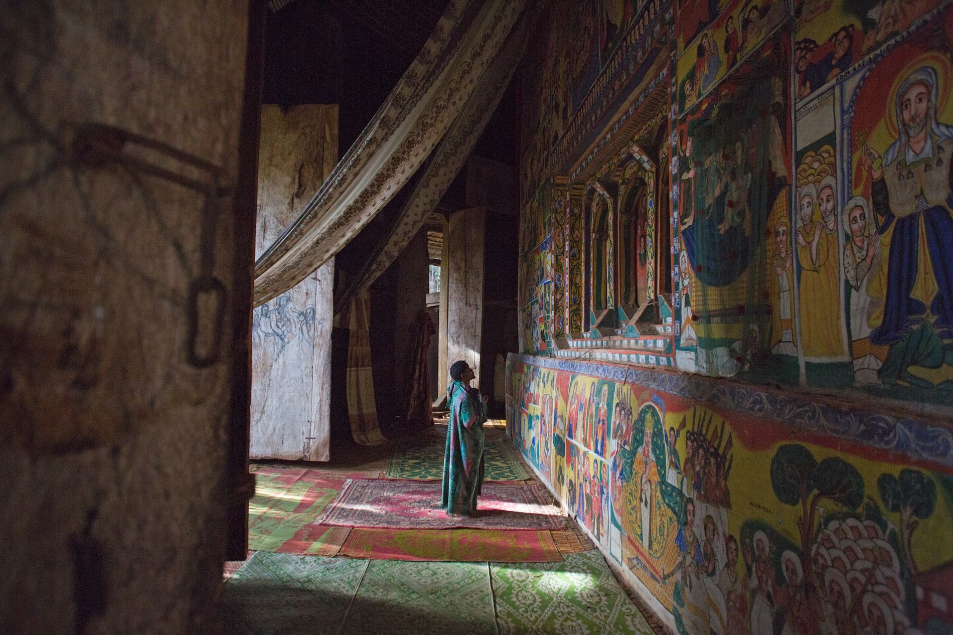The sanctum of Ural Kidane church is decorated with elaborate, ornate narrative paintings, before which a ...