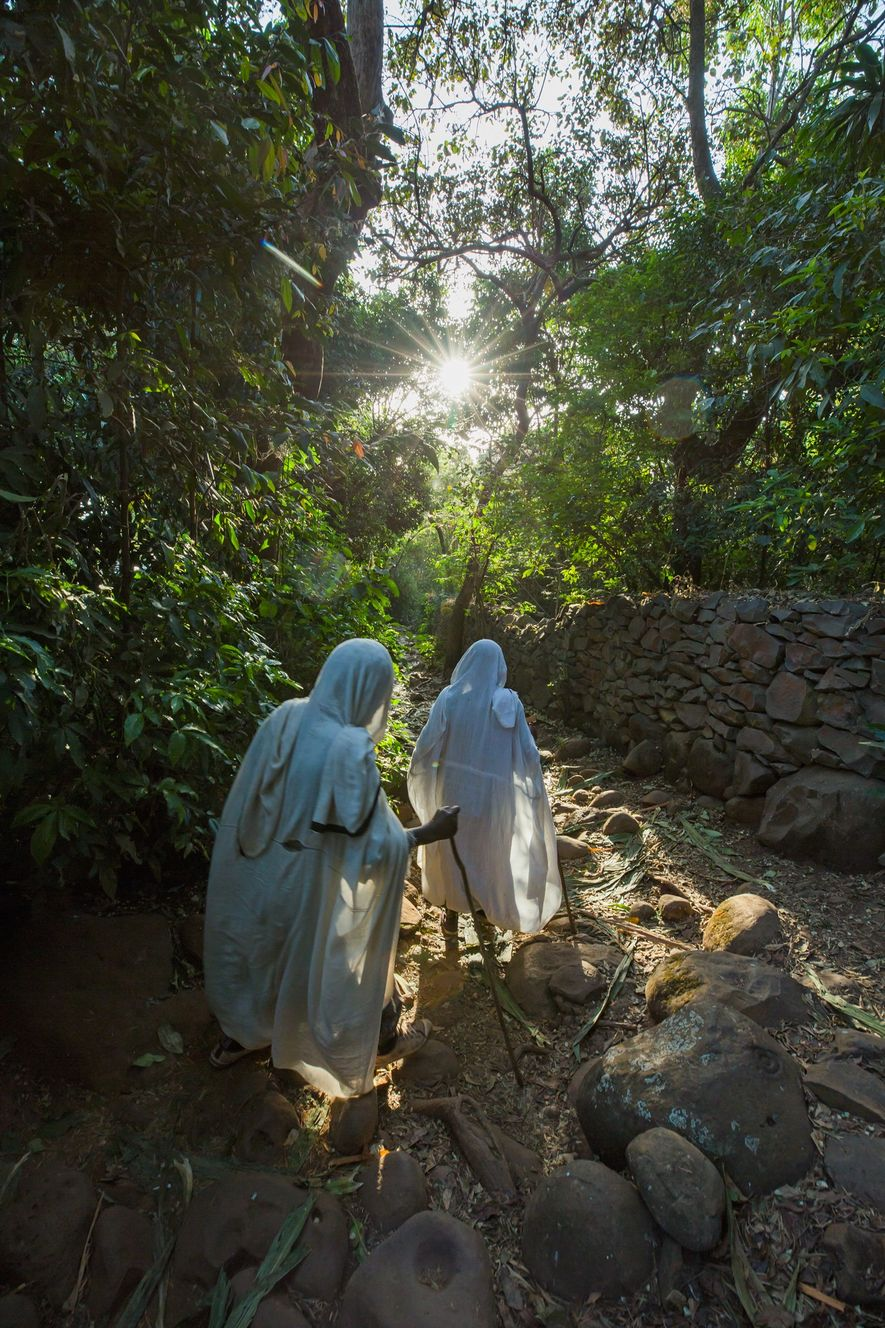 Two women walk through the church forest at the Betre Mariam church near Zege.
