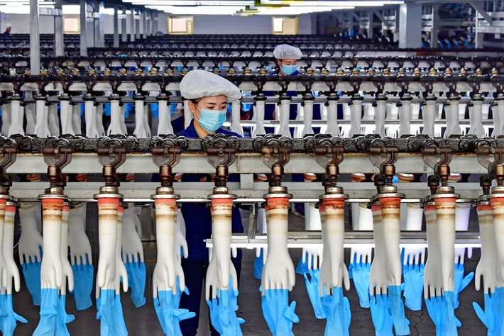 In this 2018 photo, workers produce medical gloves at a factory in Luannan County, China, which ...