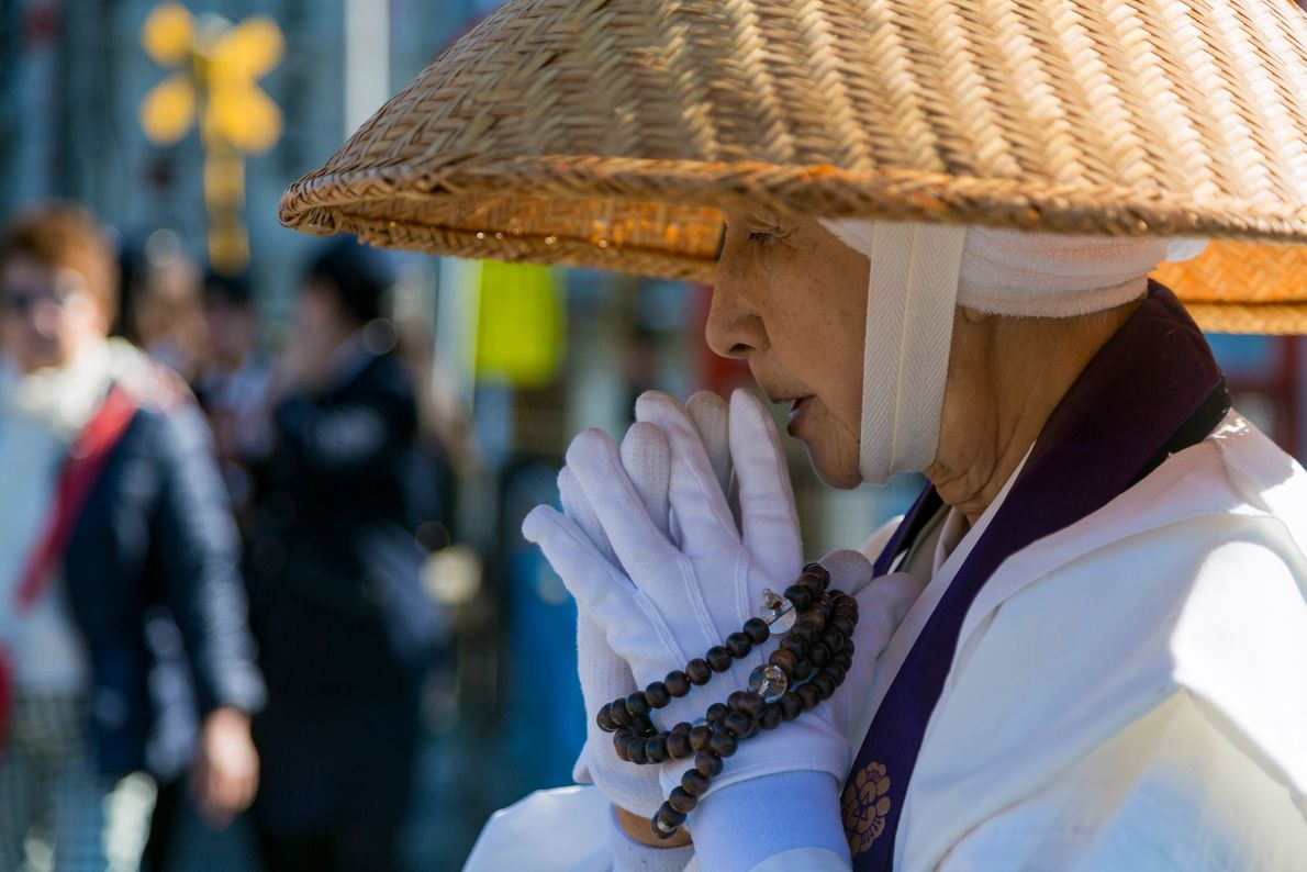 A female Buddhist monk in a pair of gloves collects alms at a temple in Kyoto, ...