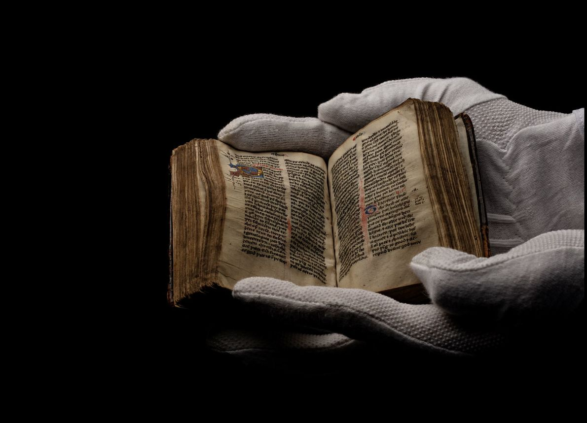 An archivist wears gloves to protect this 15th-century New Testament of the Christian Bible from damaging ...