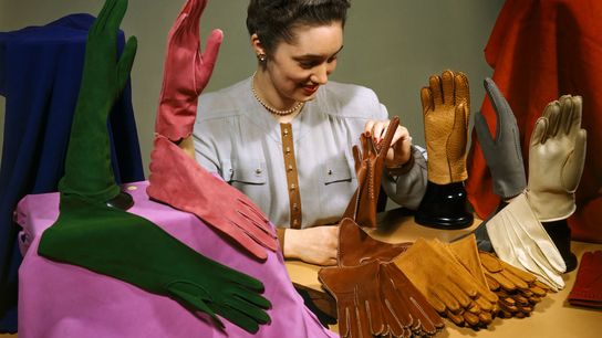 In this 1947 image, a woman examines a selection of colorful gloves. Popular for centuries as ...