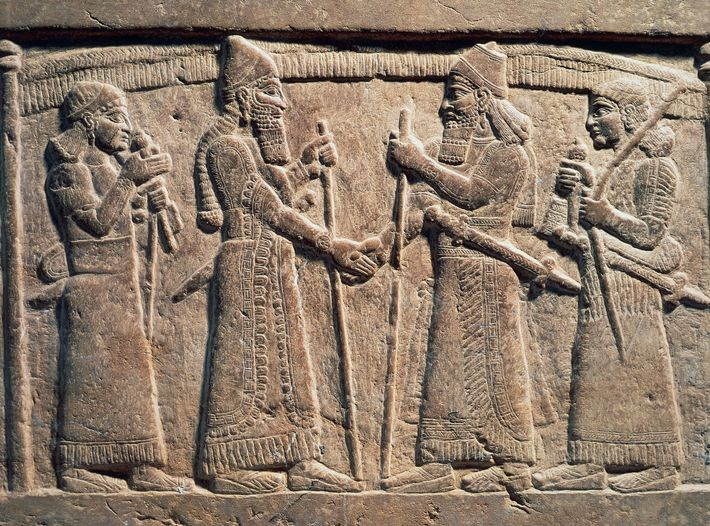 A 9th century B.C. stone relief depicts King Shalmaneser III of Assyria shaking hands with a ...