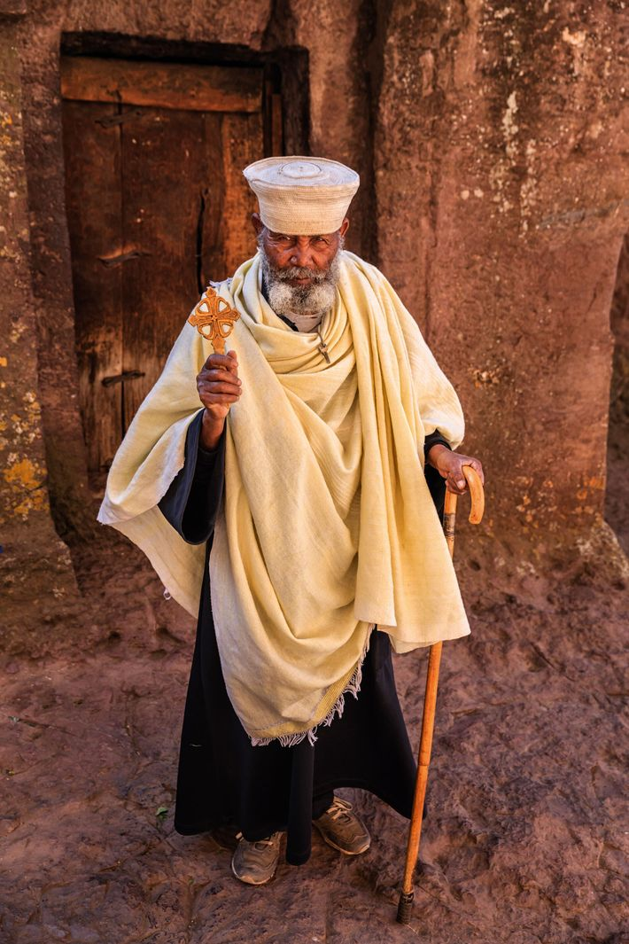 A Catholic priest stands in the front of one of the anicent rock-hewn churches in Lalibela, Ethiopia.
