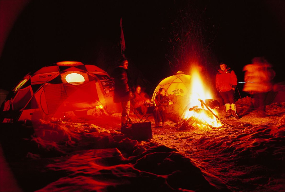 A team of Polish mountaineers share a moment of levity around a Christmas Eve bonfire at ...