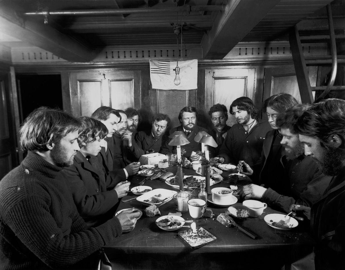 A photograph illuminated by flashlight records Christmas dinner 1901, as the men of the Baldwin-Ziegler Polar ...