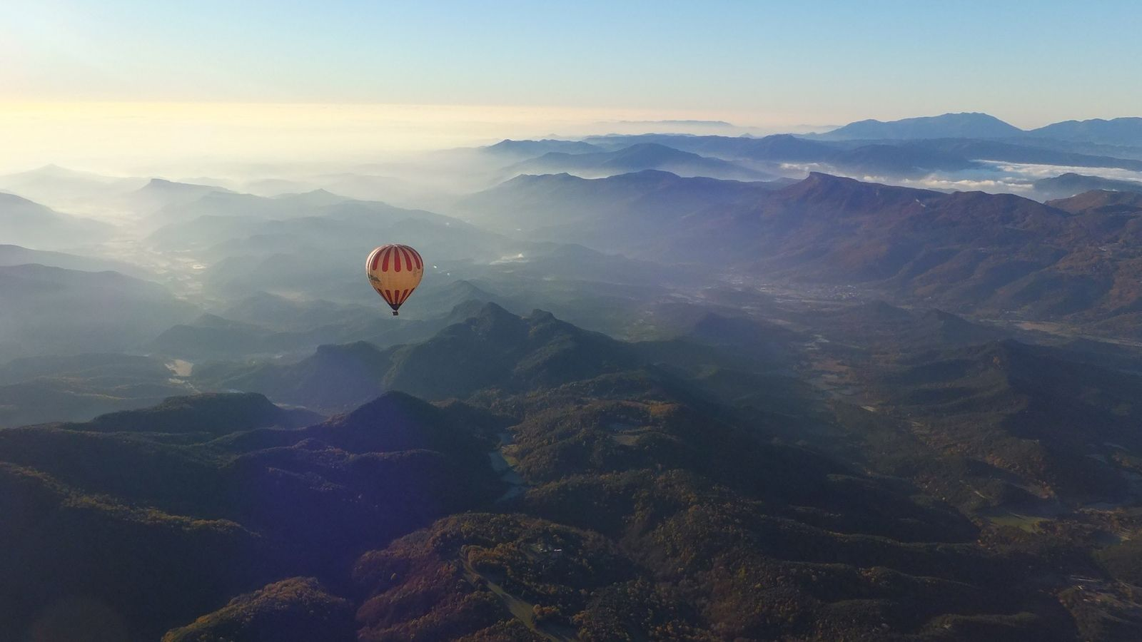 Hot-air ballon riders take in the scenic views of Garrotxa Volcanic Natural Park Catalonia.